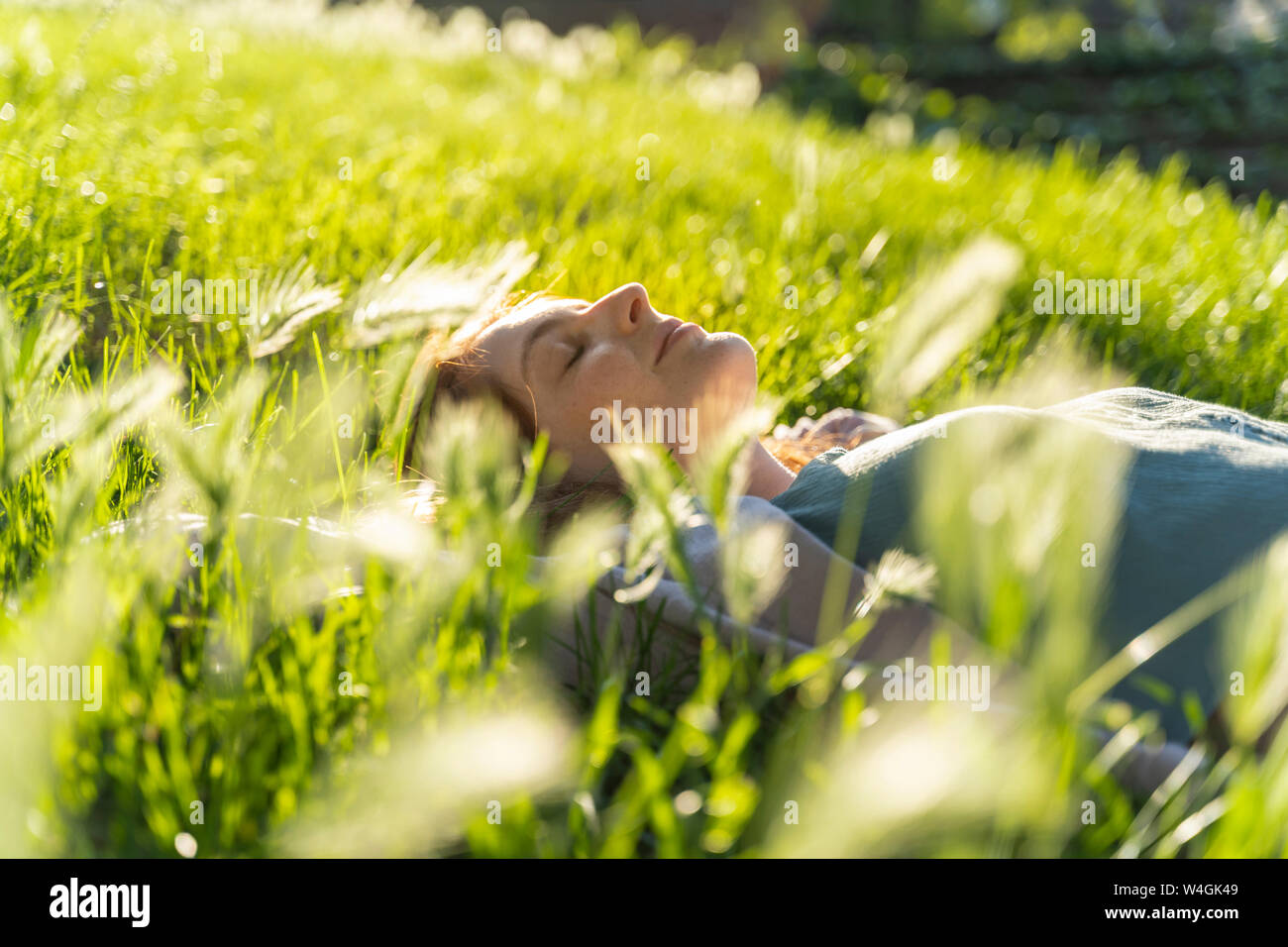 Young redheaded woman lying on meadow in a park Stock Photo