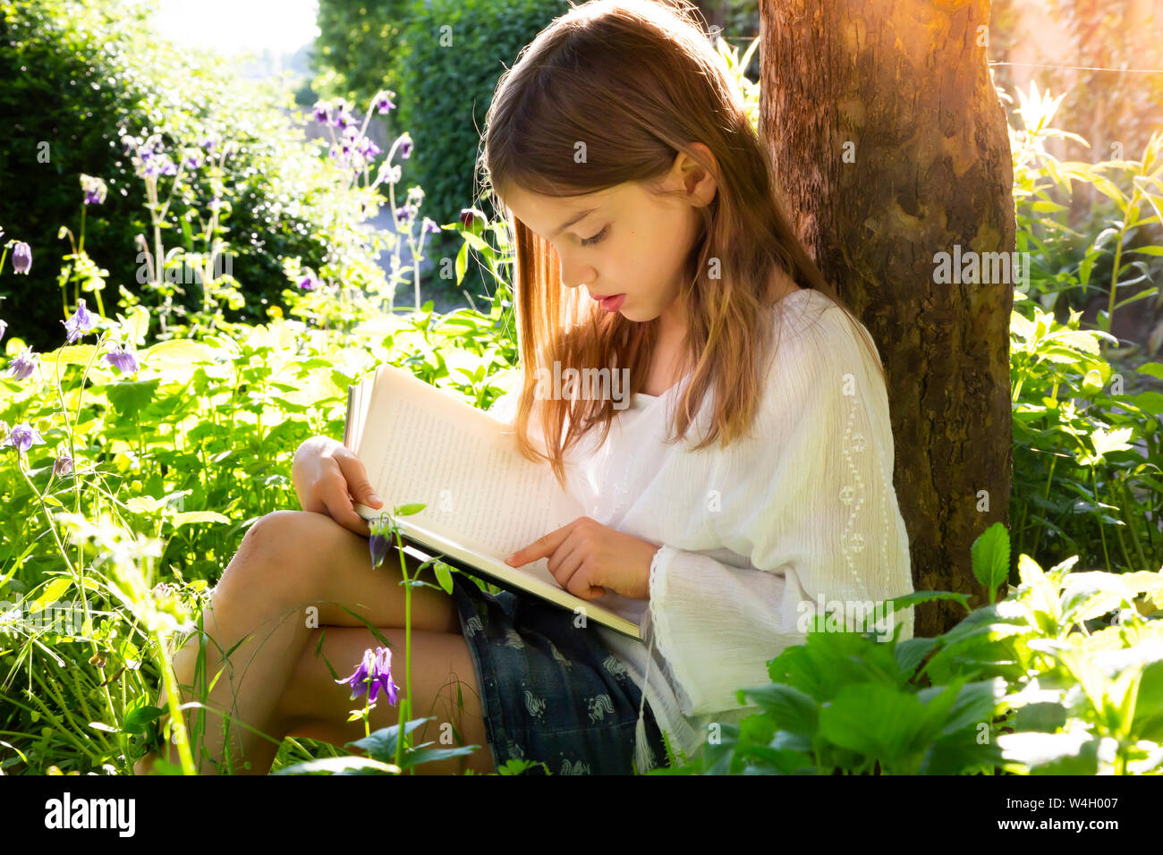 Little girl leaning against tree trunk reading a book Stock Photo