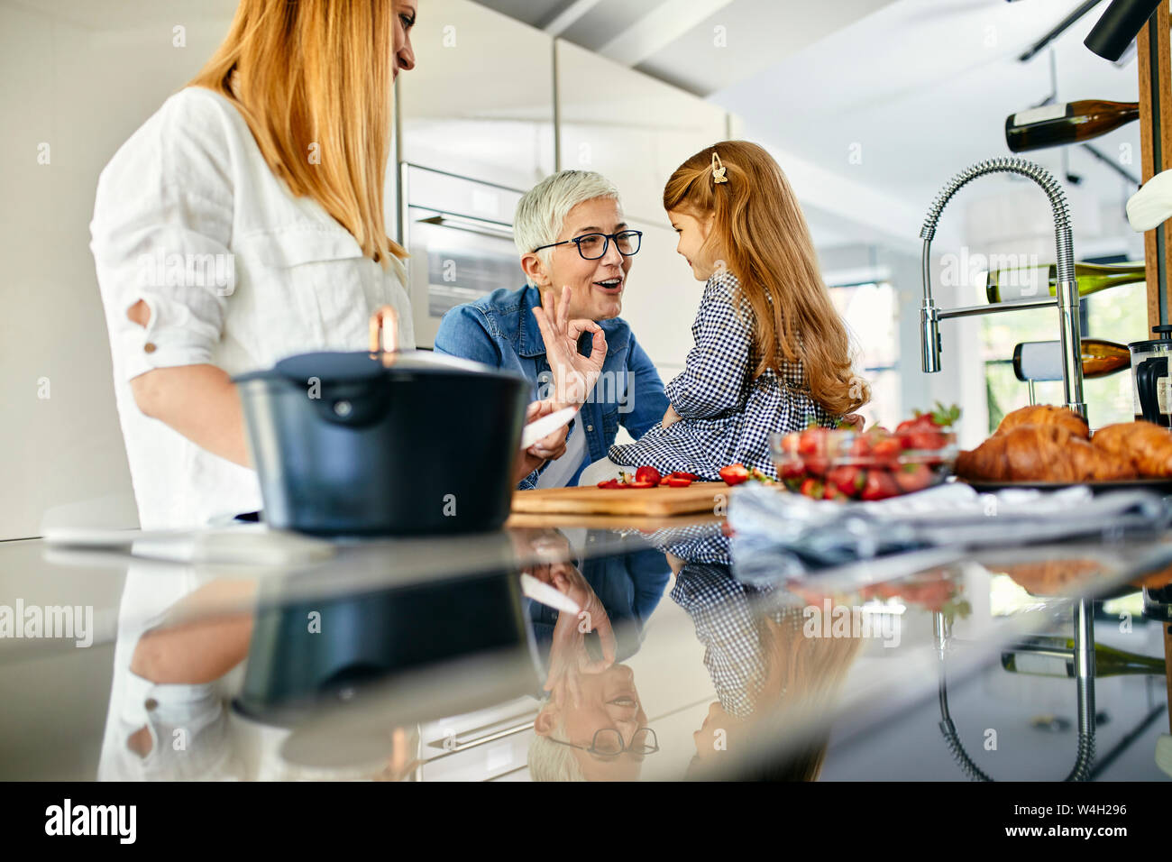 Mother, daughter and grandmother having fun, chopping strawberries in the kitchen Stock Photo