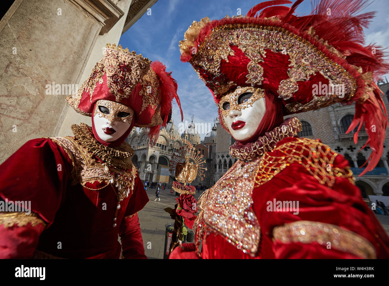 Venetian Masks in red costumes in Venice Italy Stock Photo