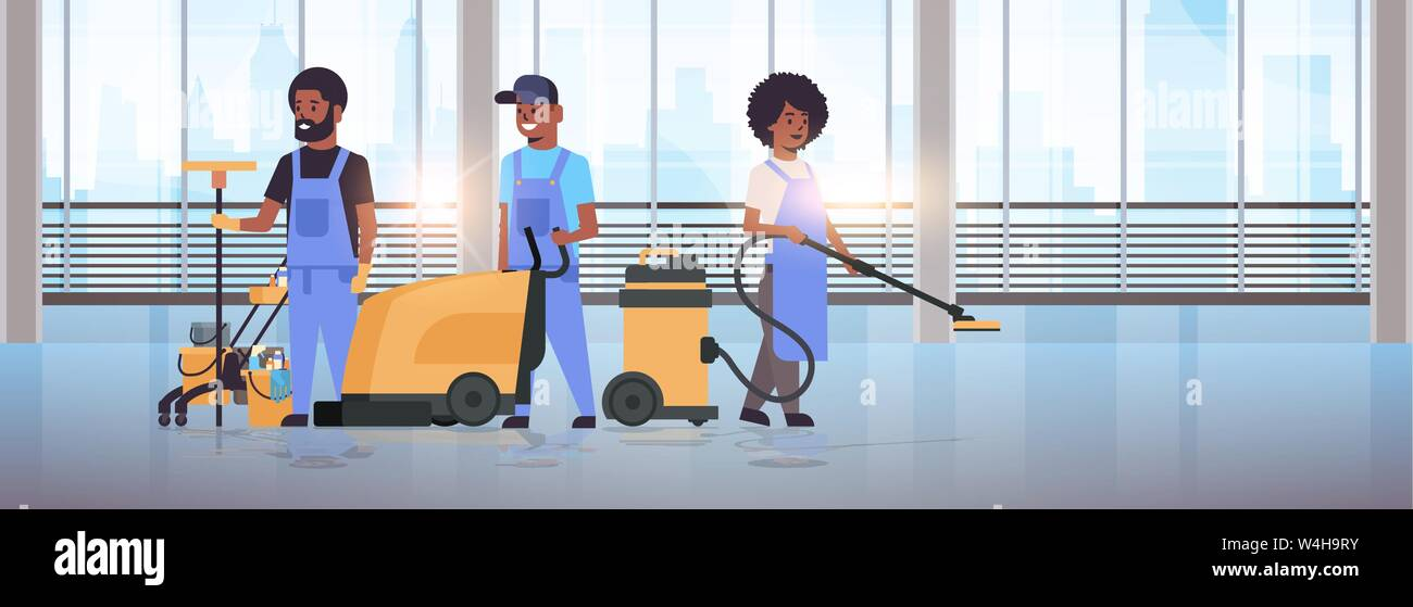 cleaners team in uniform working together cleaning service concept african american janitors using professional equipment modern hall interior Stock Vector