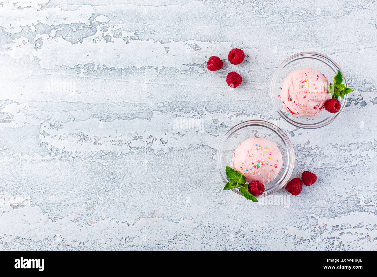 Raspberry ice cream balls with berries and mint leaves in glass bowls Stock Photo