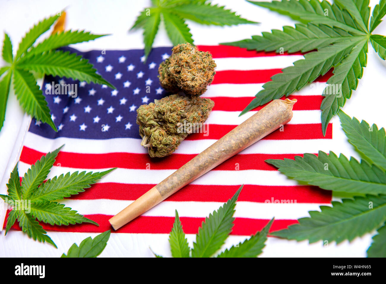 Cannabis leaves, dry nugs and rolled joint over the american flag - veteran theme medical marijuana concept Stock Photo