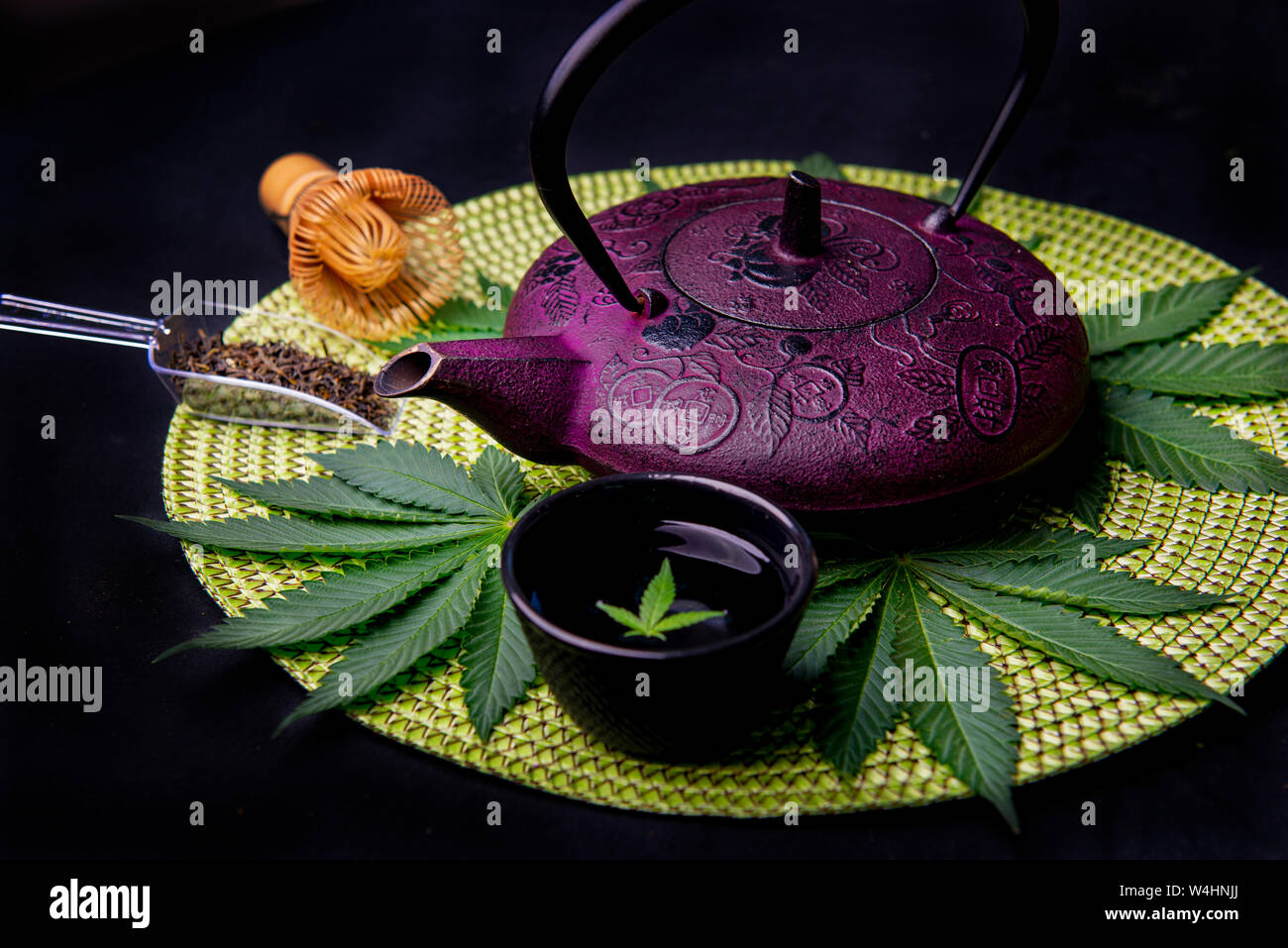 Cannabis infused tea concept with kettle and marijuana leaves isolated on black background Stock Photo