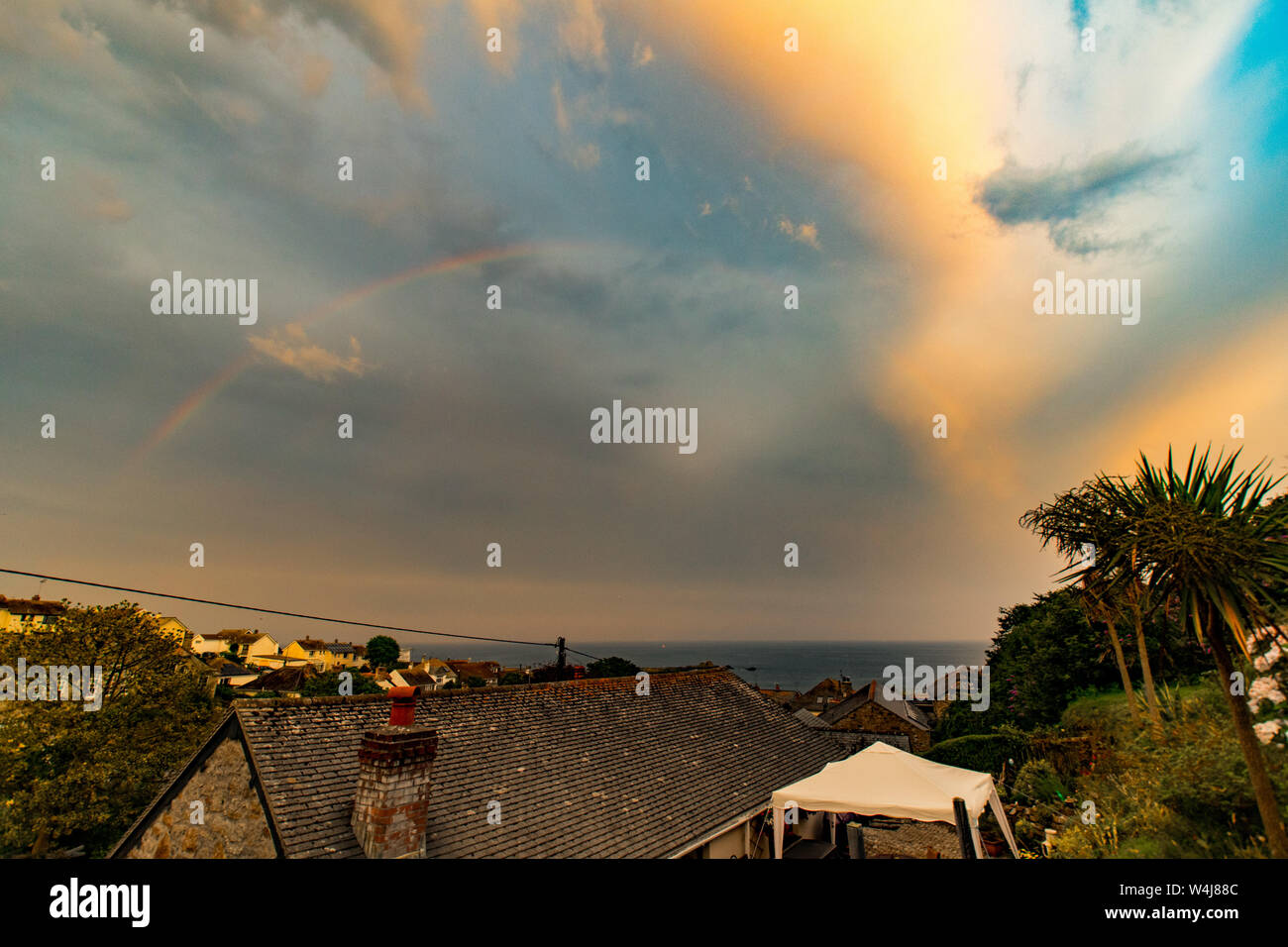 Mousehole, Cornwall, UK. 23rd July 2019. UK Weather.  Just ahead of the forecast thundery showers this rainbow made a late appearance over the town of Mousehole.  Credit Simon Maycock / Alamy Live News. Stock Photo