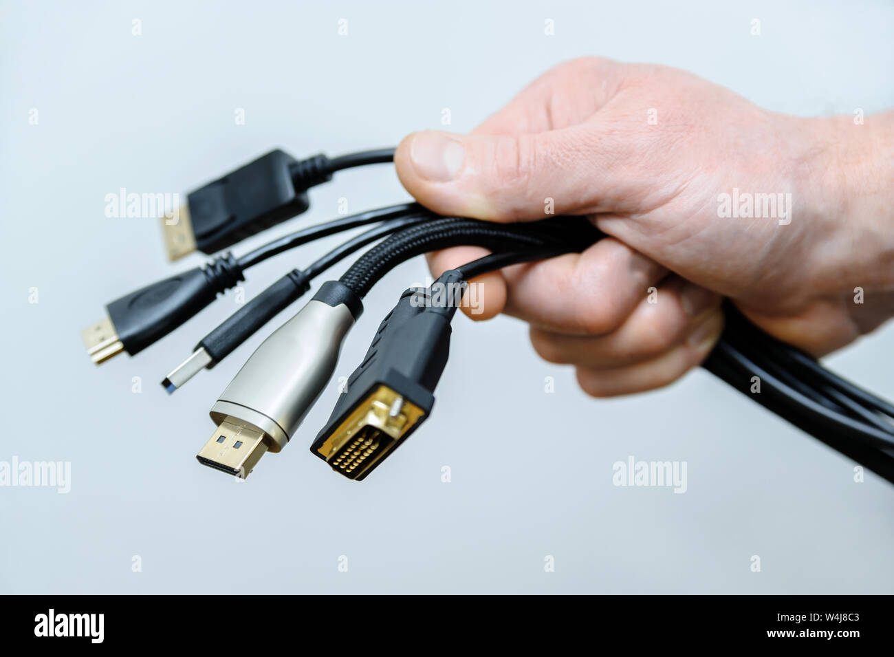 There are various cords and plugs in the hand of a man. Stock Photo