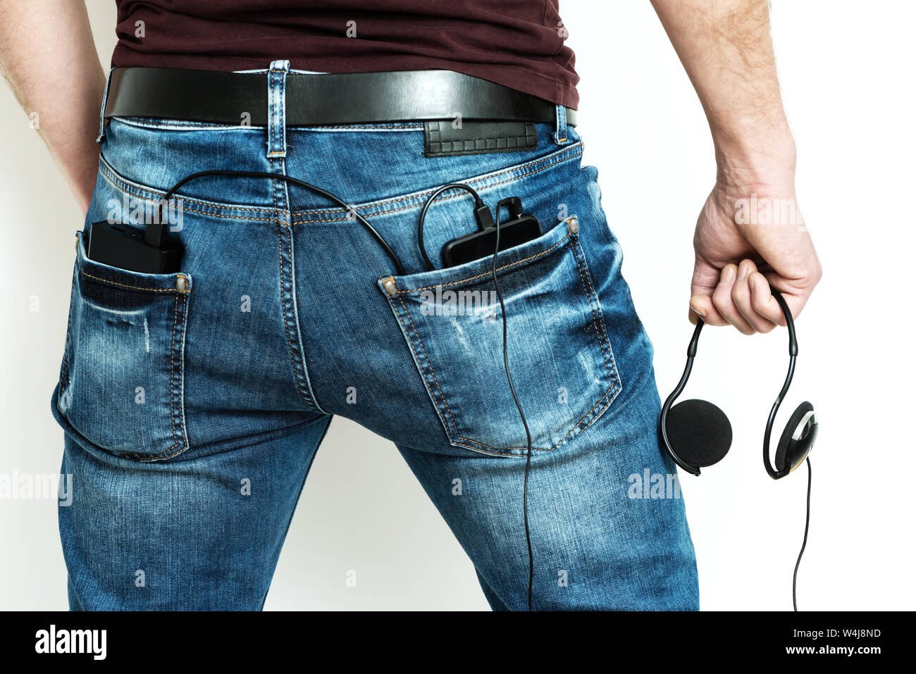 There are a power bank and smartphone in the back pocket of jeans. Stock Photo