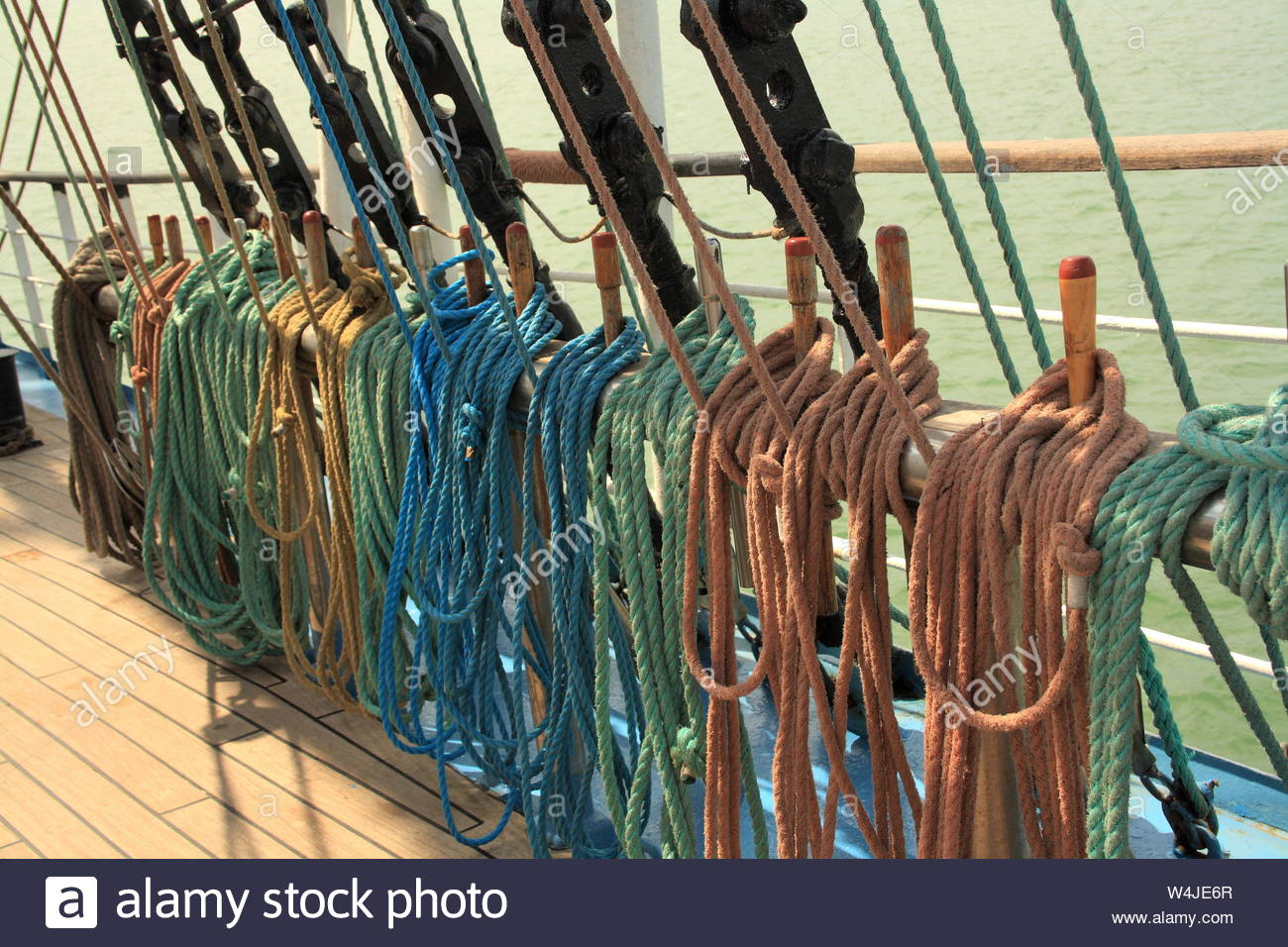 Ship multi-colored ropes on the rails. wooden deck and sea. Stock Photo