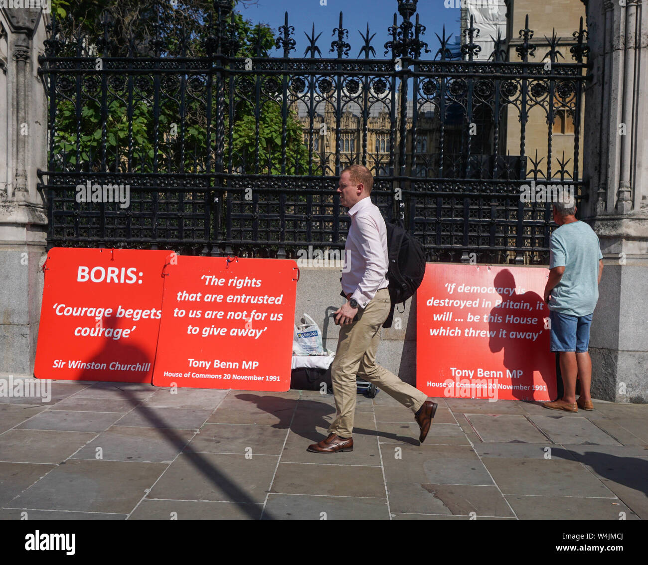 London, UK. 23rd July, 2019. A man walks past placards outside the Houses of Parliament. Credit: Yiannis Alexopoulos/SOPA Images/ZUMA Wire/Alamy Live News Stock Photo