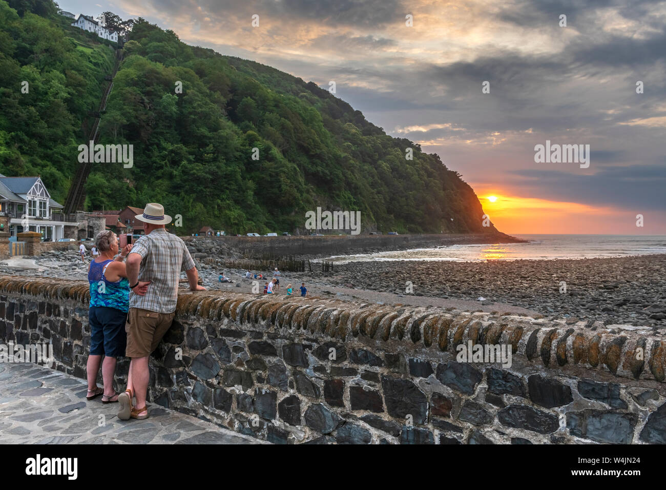 Lynmouth Harbour, North Devon, England. Tuesday 23rd July 2019. UK Weather. The calm before the storm. After a hot summers day in North Devon, at sunset people still play on the beach as a couple record the colourful sunset  over the picturesque little harbour in Lynmouth. Credit: Terry Mathews/Alamy Live News Stock Photo