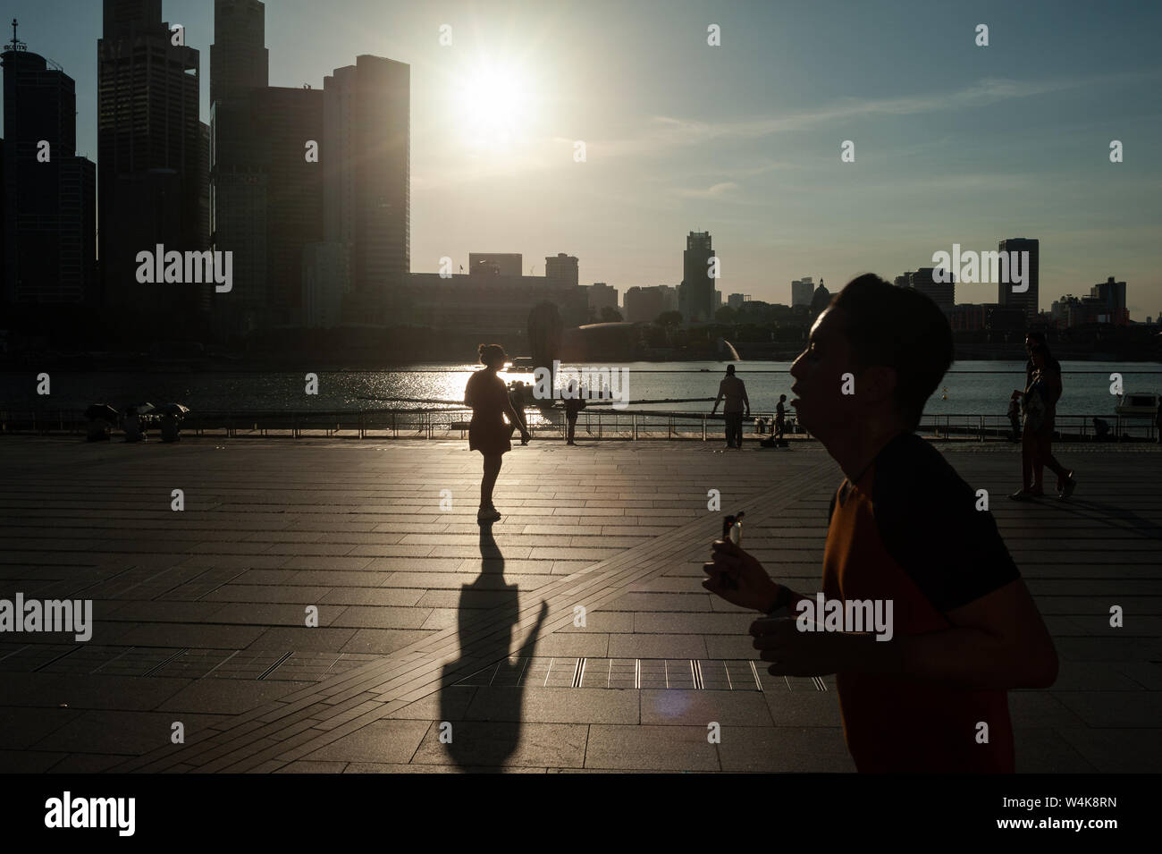 19.07.2019, Singapore, Republic of Singapore, Asia - People at the waterfront in Marina Bay with the city skyline of the central business district. Stock Photo