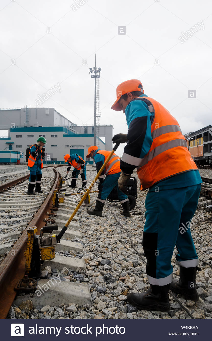 Tobolsk, Russia - July 15. 2016: Sibur company. Denisovka railway station. Railway workers repairing rails in rainy weather Stock Photo