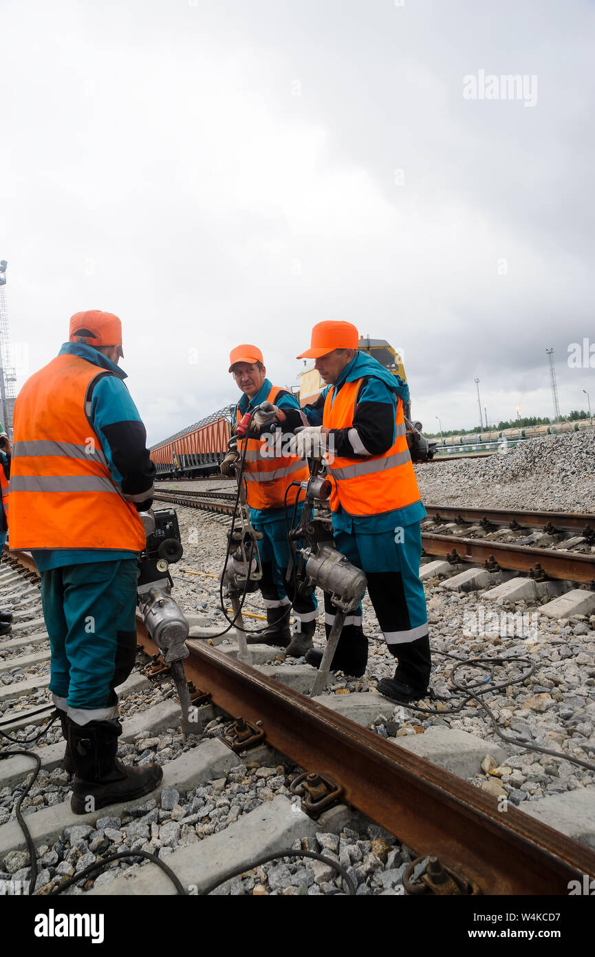 Tobolsk, Russia - July 15. 2016: Sibur company. Denisovka railway station. Railway workers repairing rails in rainy weather Stock Photo