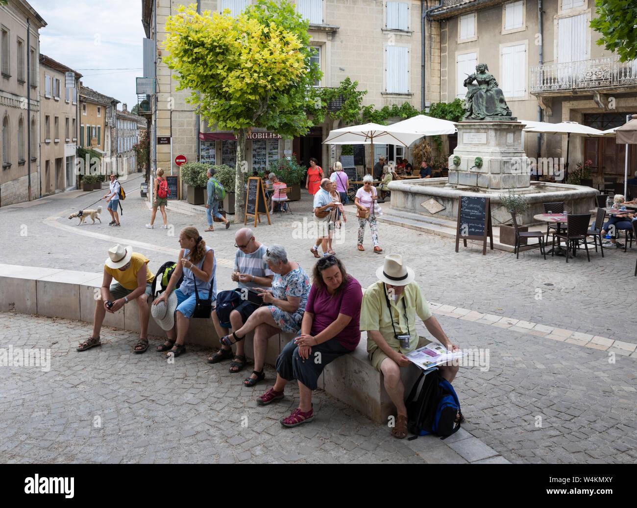 Tourists resting in the Place Sévigné, Grignan, Drome department, Auvergne-Rhone-Alpes, Provence, France, Europe Stock Photo