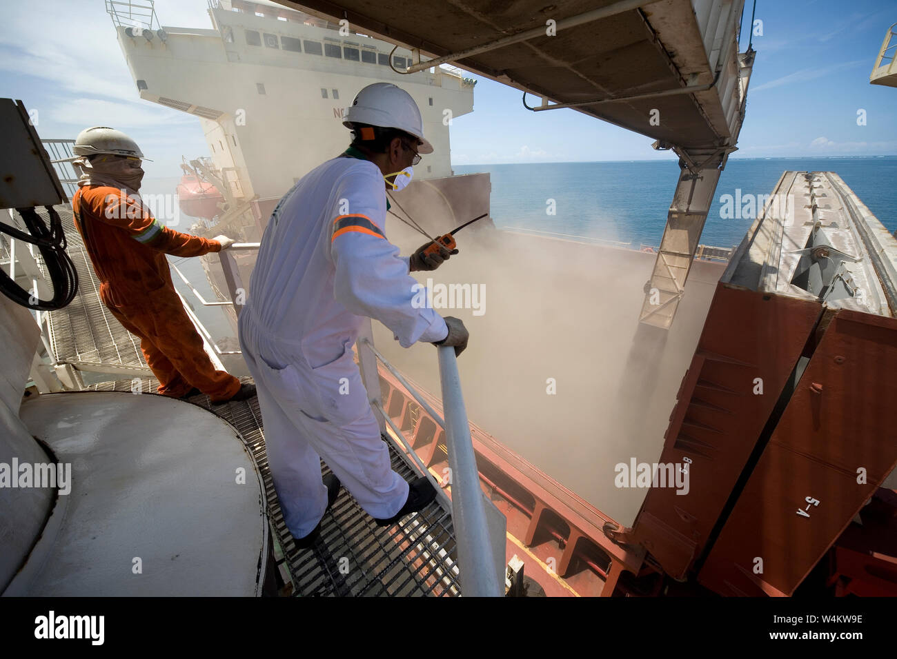 Mining, managing & transporting of titanium mineral sands. Boom operator & loading master on barge overseeing discharge of product into OGV cargo hold Stock Photo