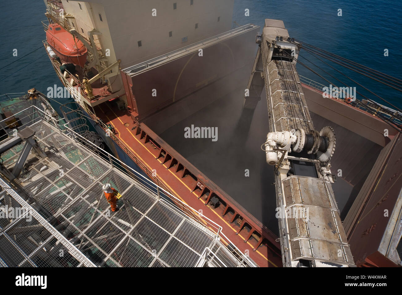 Mining, managing & transporting of titanium mineral sands. Loading mineral sands cargo via transhipment barge boom into hold of bulk carrier at sea. Stock Photo