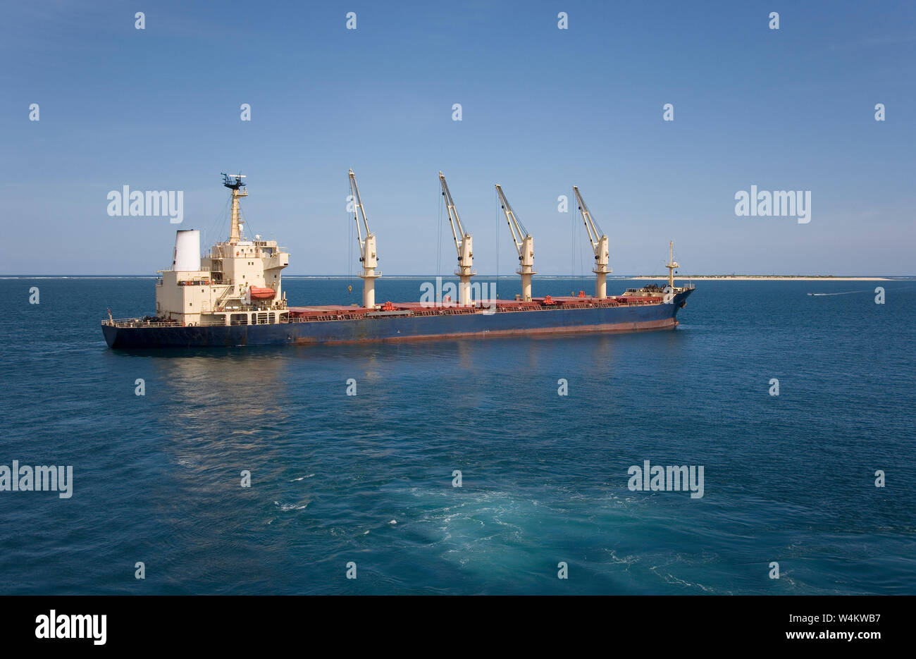 Mining, managing & transporting of titanium mineral sands. Bulk carrier with cargo of titanium mineral sands leaving deep water transhipment point. Stock Photo