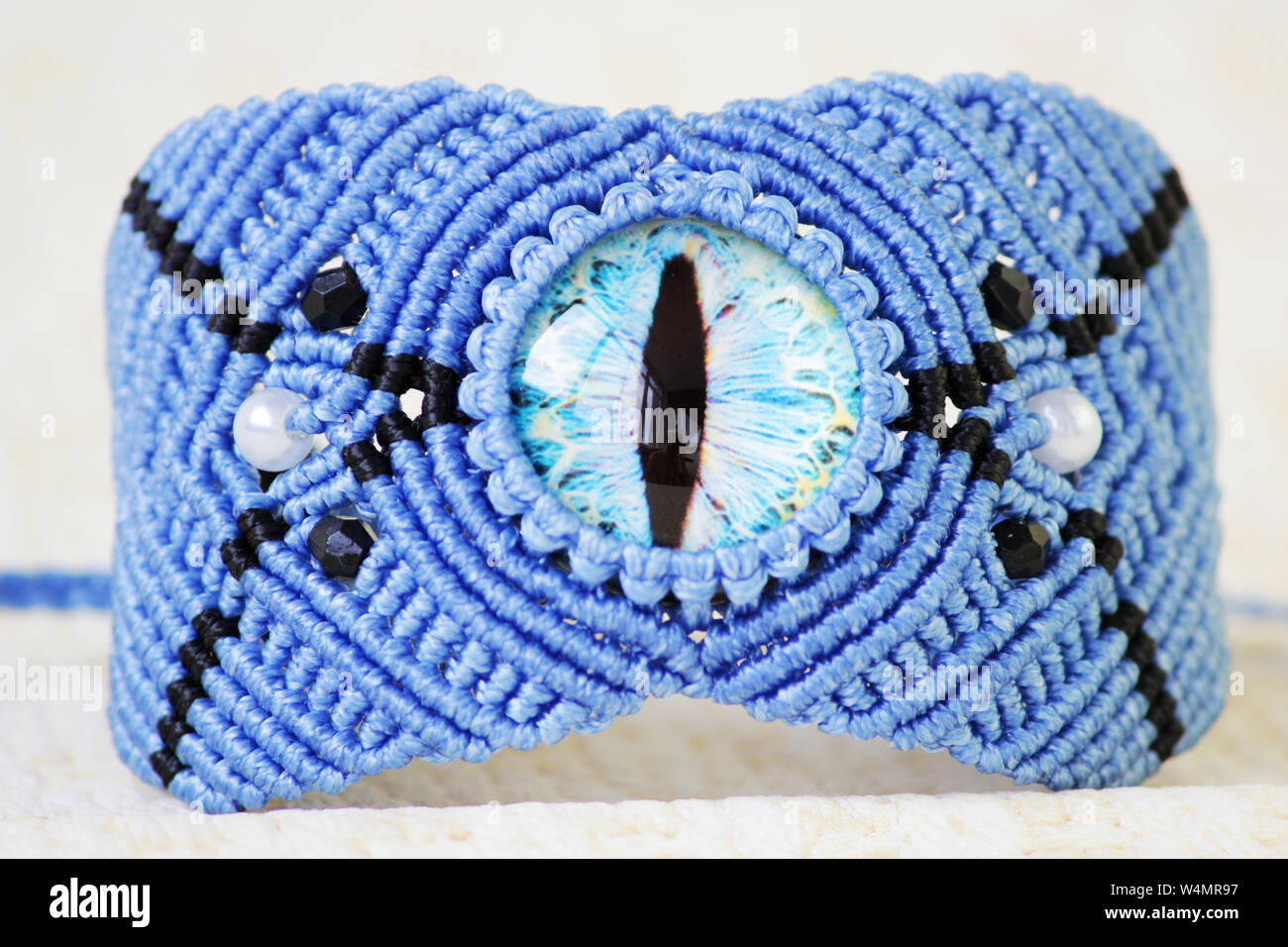 blue bracelete with white beads and the dragon's eye on the hand from waxed thread in the technique of macrame. Handmade Stock Photo