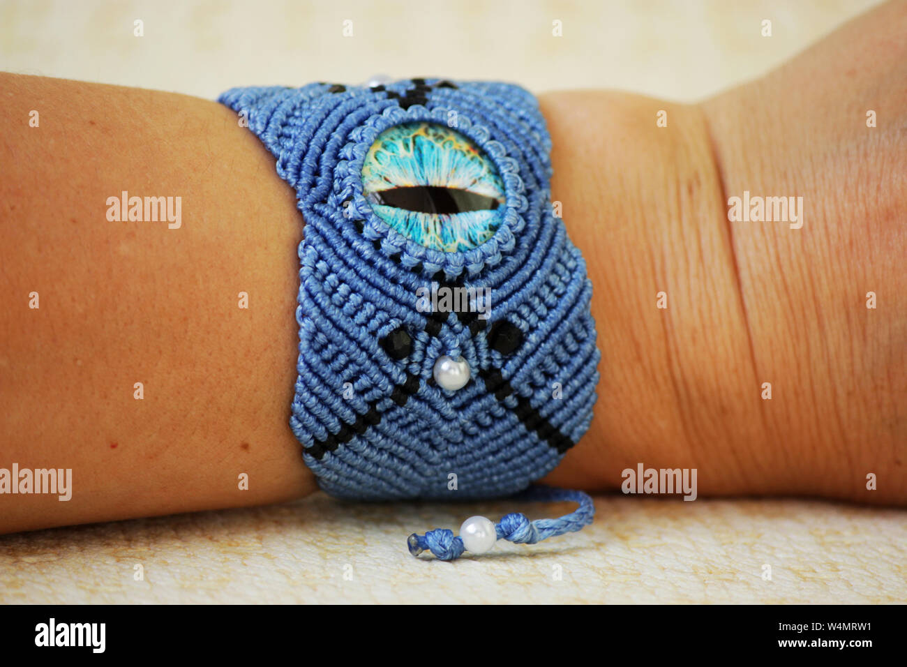 blue bracelete with white beads and the dragon's eye on the hand from waxed thread in the technique of macrame. Handmade. put on hand. Stock Photo