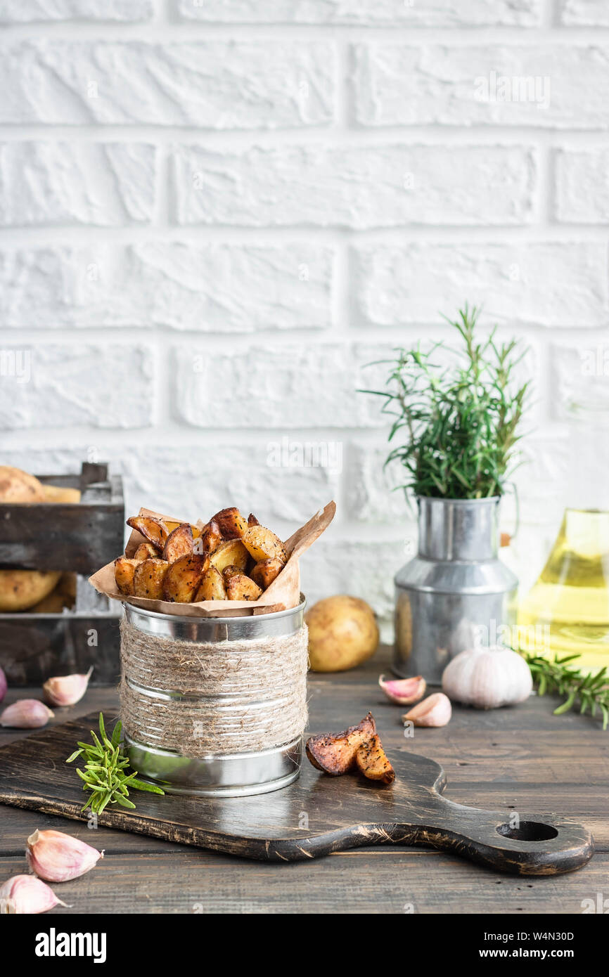 Baked young potatoes in a rustic style with rosemary, garlic and sumac as a concept of simple and delicious food and an alternative to french fries. Stock Photo