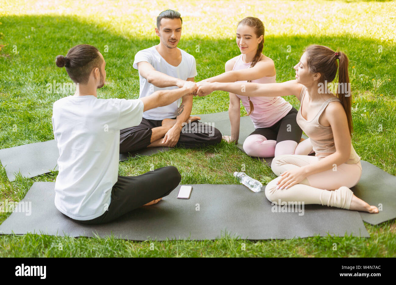 Group of fit happy people fist bumping, celebrating success. Stock Photo