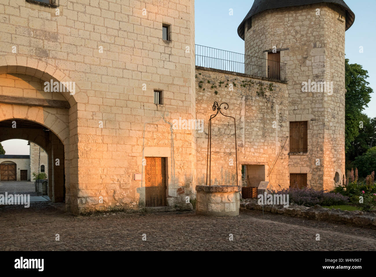 The evening sun lighting up the inner courtyard walls and old well. Chateau du Rivau, Loire Valley, France Stock Photo