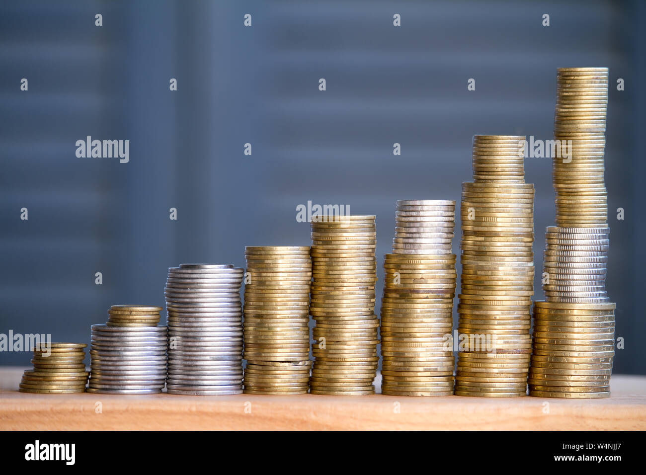Closeup of columns of multi-colored coins of increasing height, the concept of saving and saving money, selective focus Stock Photo