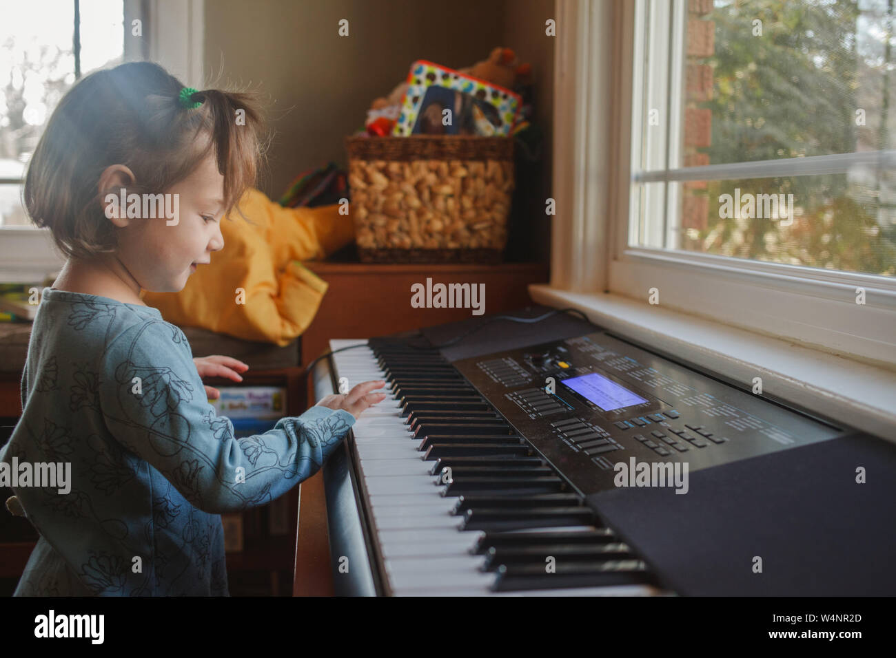 portrait of a cute little child playing piano in front of a window Stock Photo