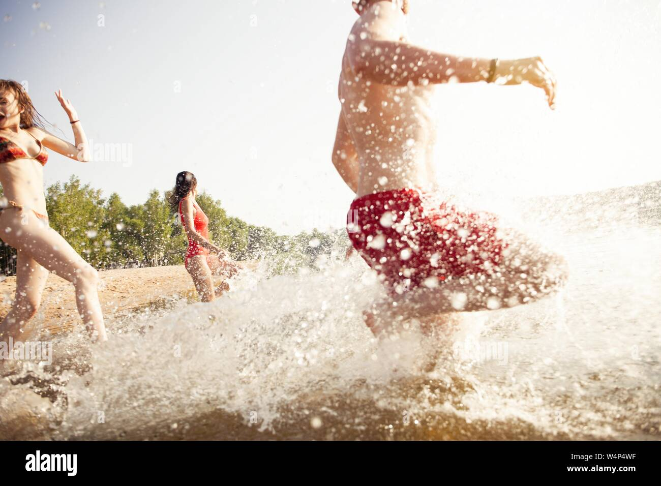 Group of happy friends running in to water - active people having fun on the beach on vacation Stock Photo