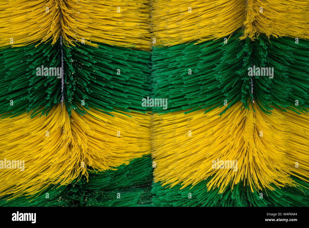 Big brushes of automatic machine Car Wash. Caring for a vehicle. Colored dynamic background Stock Photo