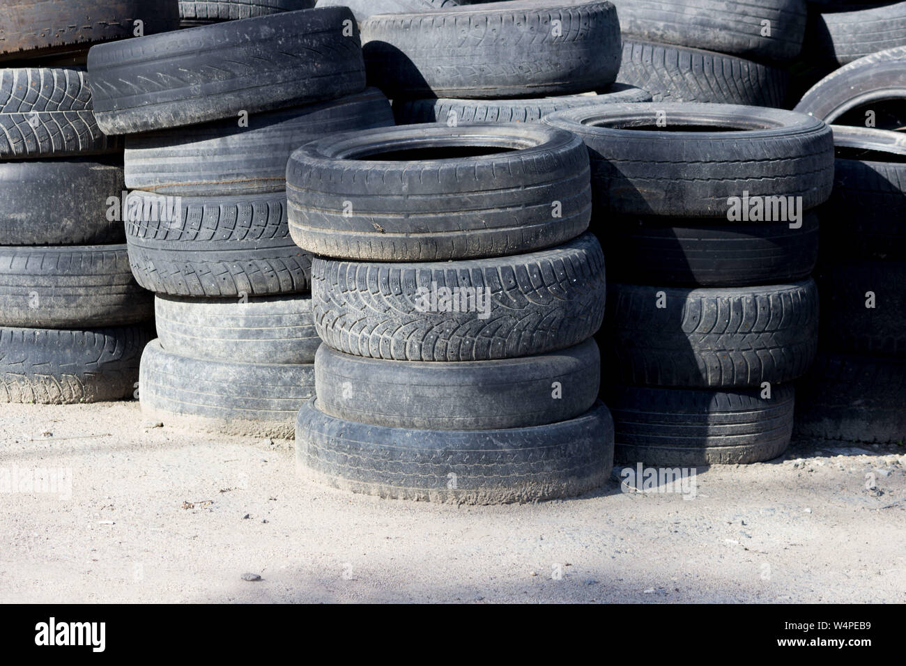 old car tires stacked near the forest. concept of ecological disaster and illegal dumps. Stock Photo