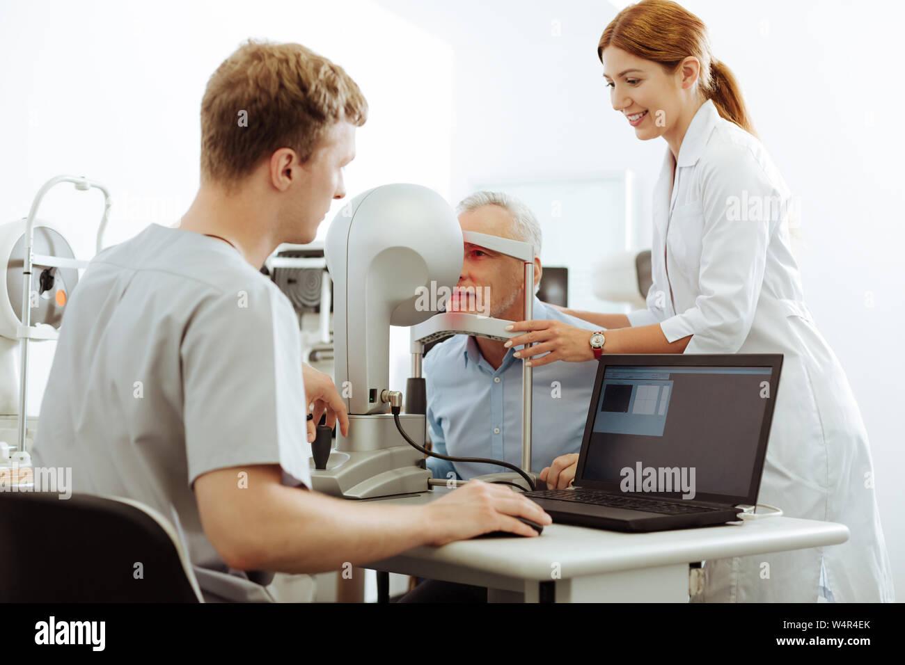 Nurse Assisting Patient Pleasant Helpful Nurse Assisting Patient Visiting Eye Specialist In Private Clinic Stock Photo Alamy