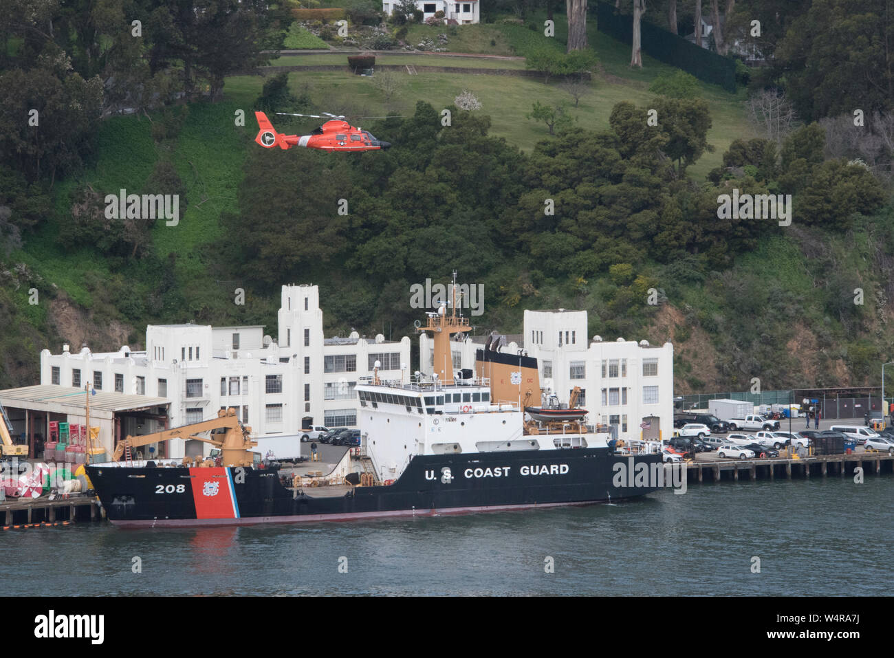 A Coast Guard Air Station San Francisco MH-65 Dolphin helicopter flies over the Coast Guard Cutter Aspen and Coast Guard Sector San Francisco during a formation flight, April 15, 2019. Air Station San Francisco's primary missions include search and rescue, port, waterways, and coastal security, protecting living marine resources, enforcing federal and international laws and regulations and providing logistical support to other Coast Guard units. (U.S. Coast Guard photo by Petty Officer 2nd Class Jordan Akiyama.) Stock Photo
