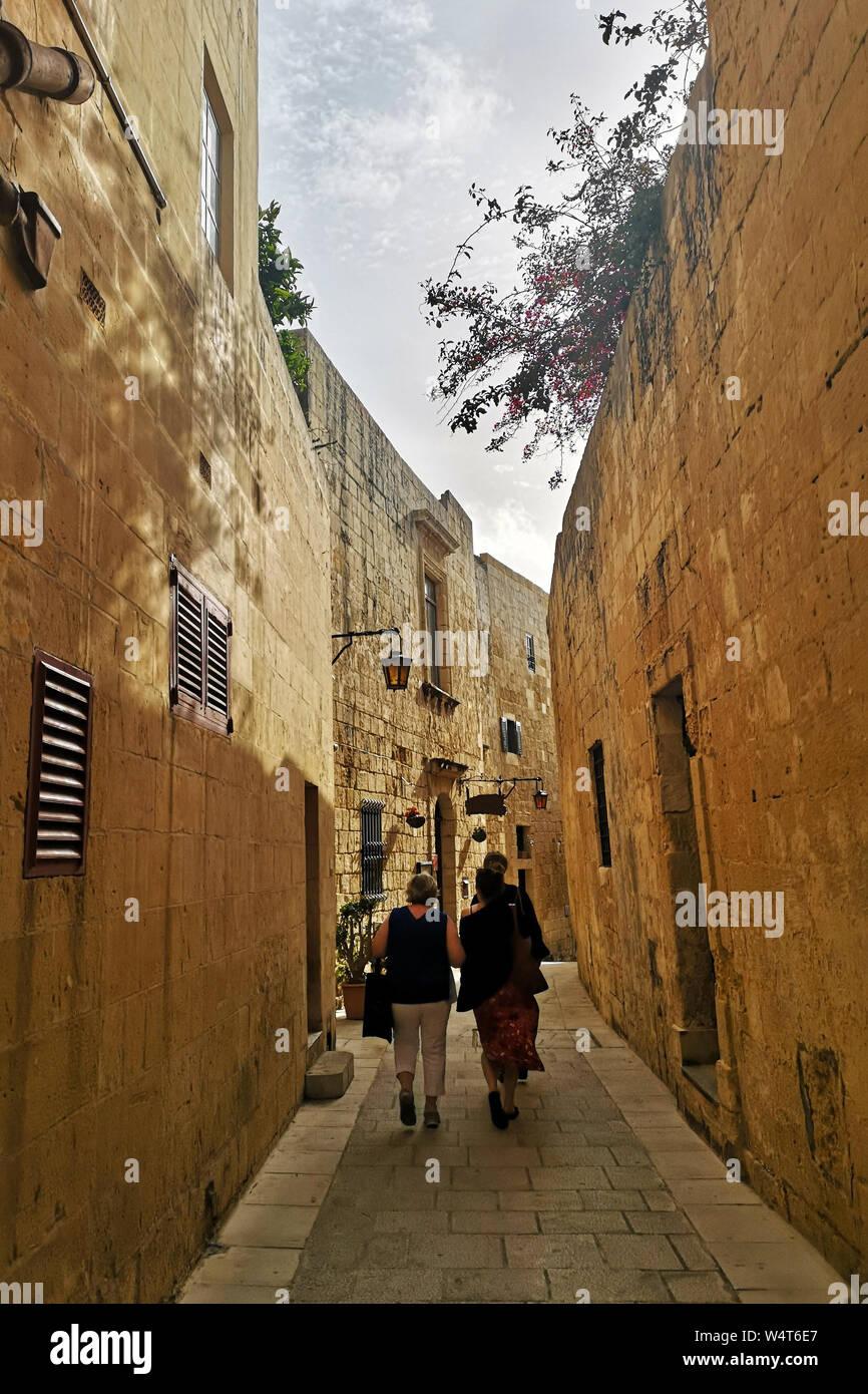 Three people walking the streets of Medina, Malta Stock Photo