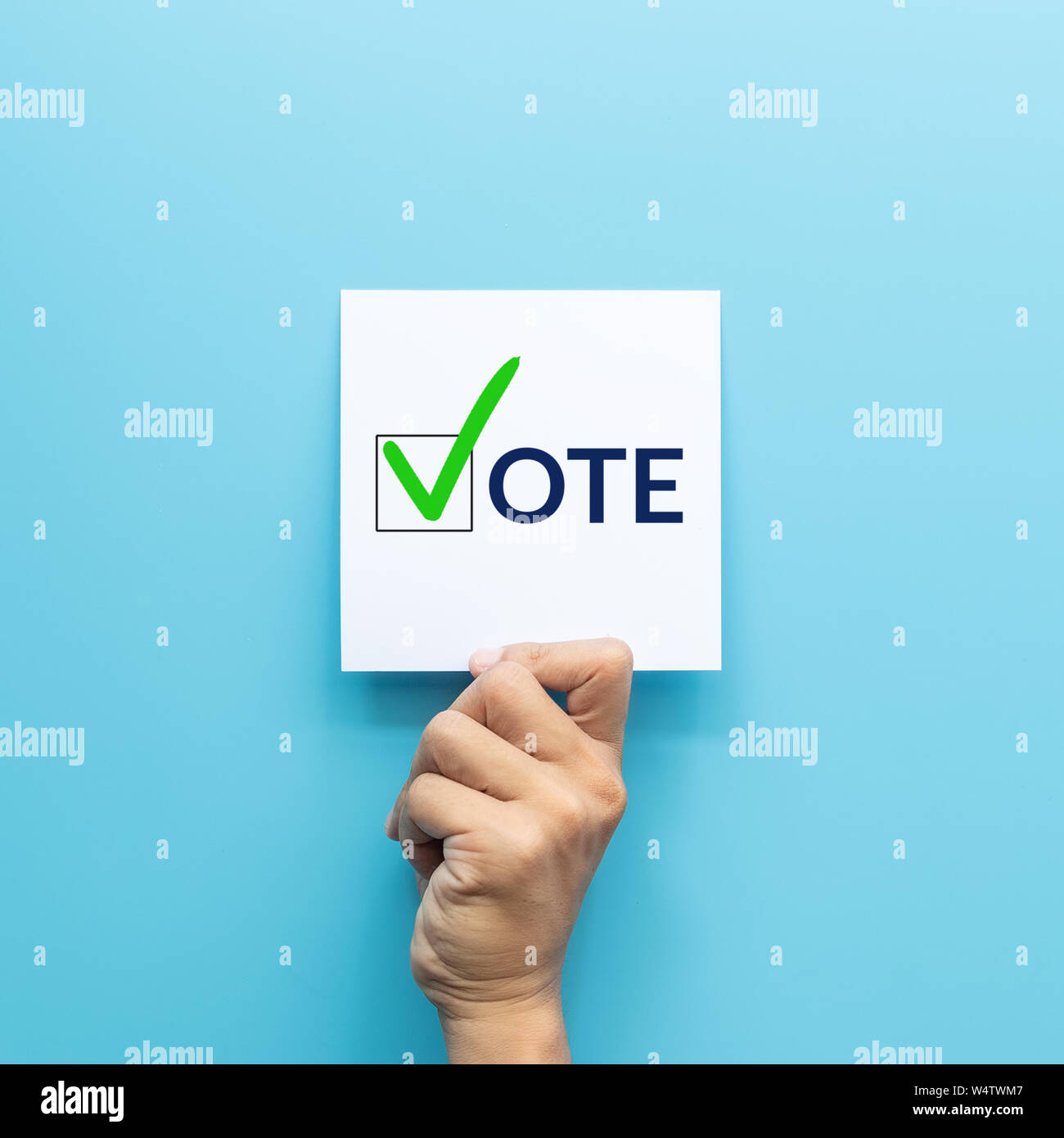 """hand holding white paper with the """"vote"""" and green check mark voting symbols in checkbox of the inscription isolated on blue background Stock Photo"""