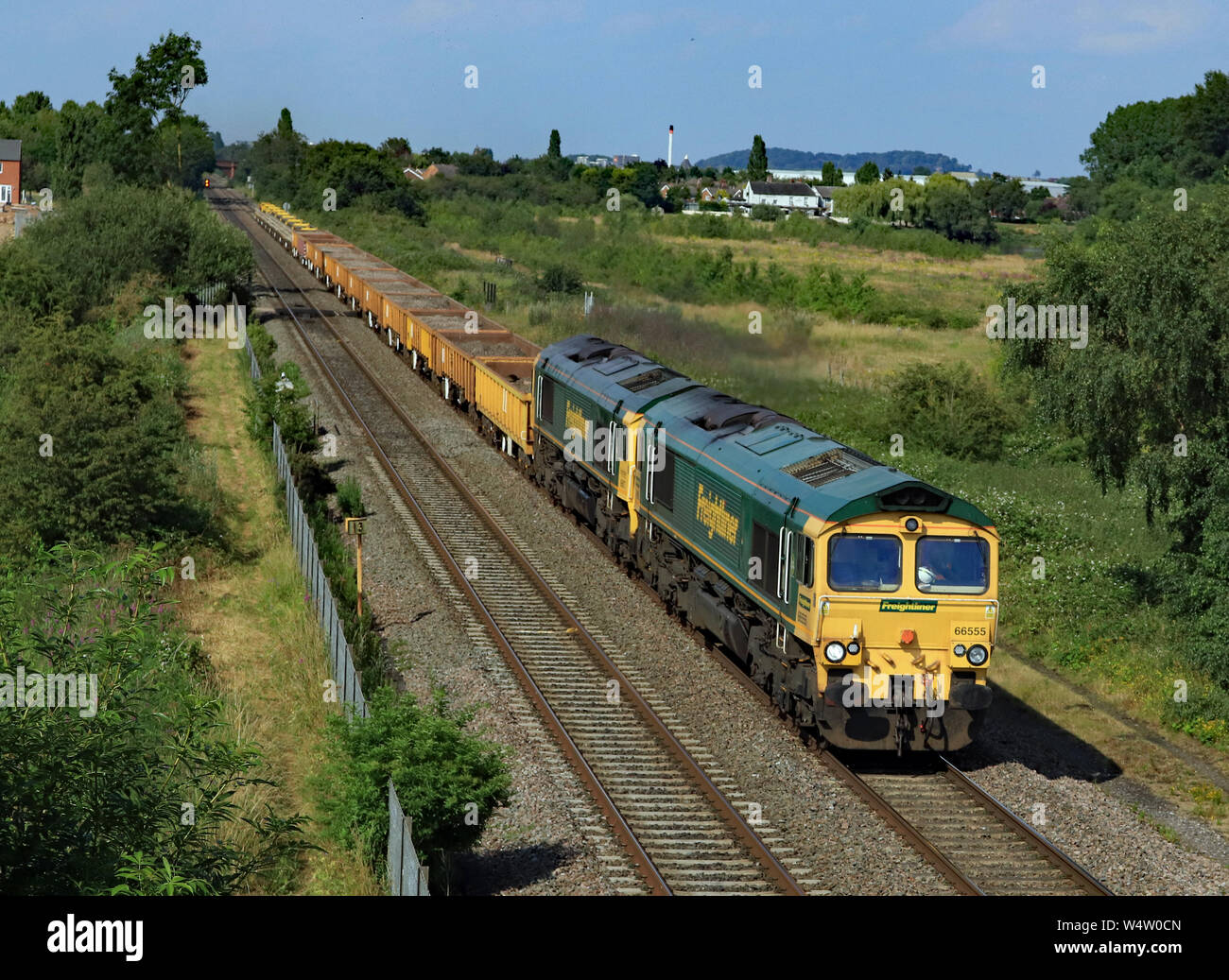 Freightliner diesel locomotives 66555 and 66617 travelling from Burton on Trent towards Tamworth with a freight train pass Branston in Staffordshire. Stock Photo