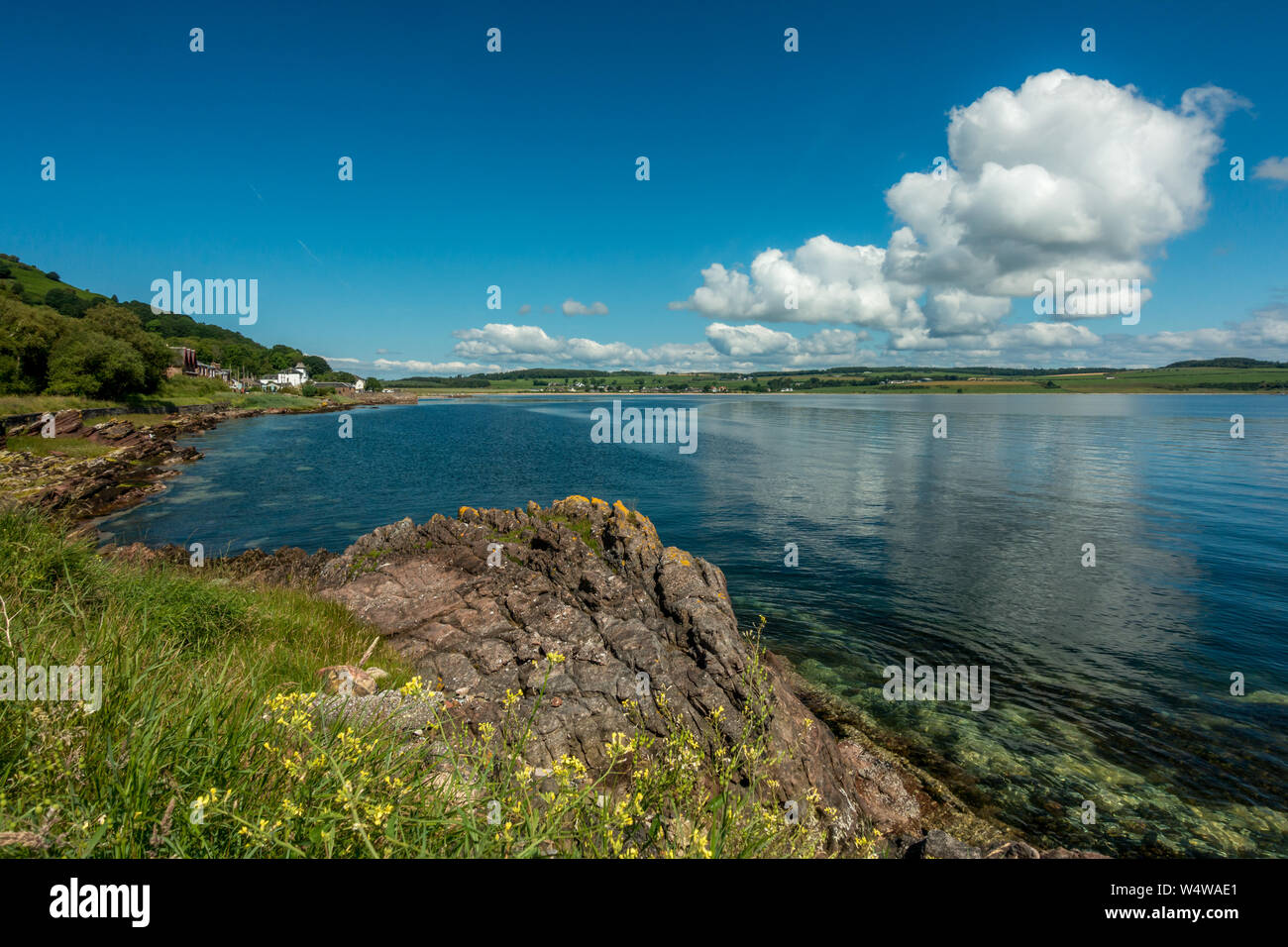 Clear water and blue skies on a beautiful sunny day on the coast at Kilchattan Bay, Isle of Bute, Scotland Stock Photo