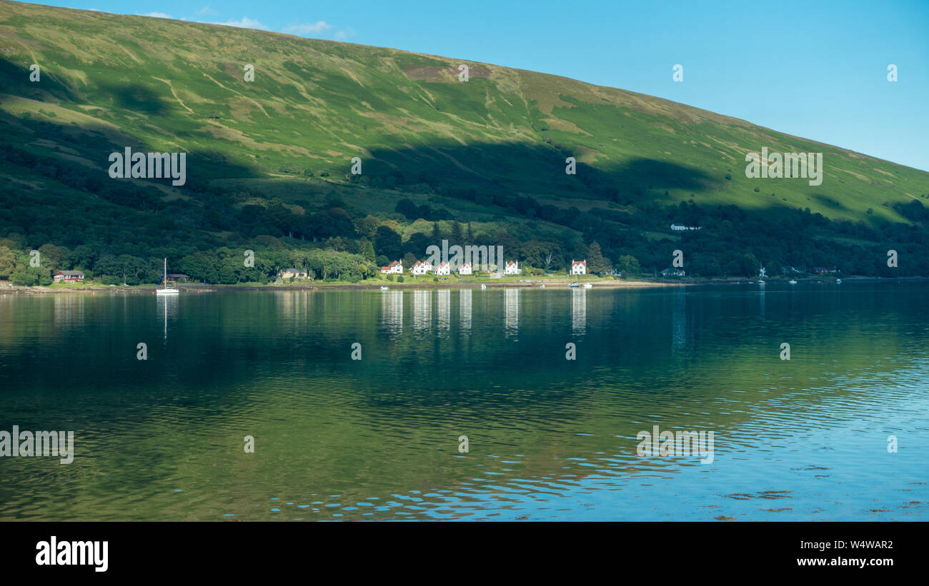 The stunning coastline around the Kyles of Bute, image of Colintraive houses with reflections taken from Rhubodach, Isle of Bute Stock Photo