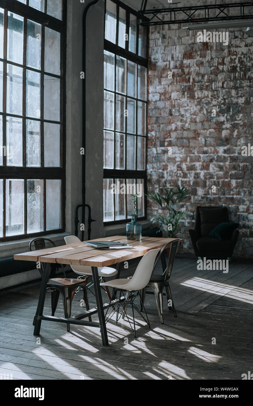 A simple loft-style interior with brick walls, a large window, a wooden table, chairs in different styles and a tropical palm tree Stock Photo