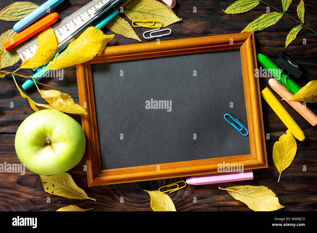 Frame Background Back to school. Table with autumn leaves, note pad, apple  and school supplies. Free space for your text. Stock Photo