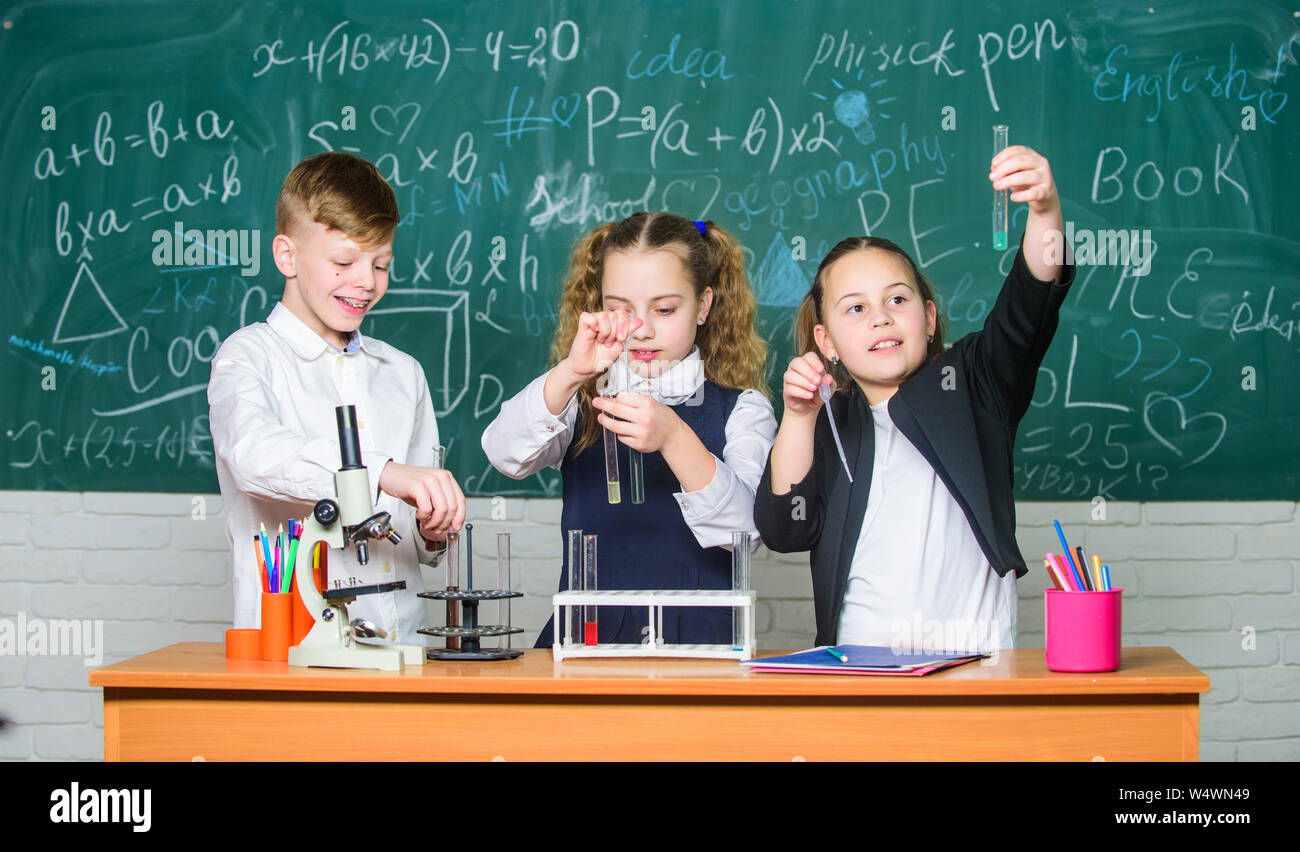 Organic chemistry is study of compounds containing carbon. Basic chemical reactions. Fascinating chemistry. Group school pupils study chemistry in school. Boy and girls enjoy chemical experiment. Stock Photo