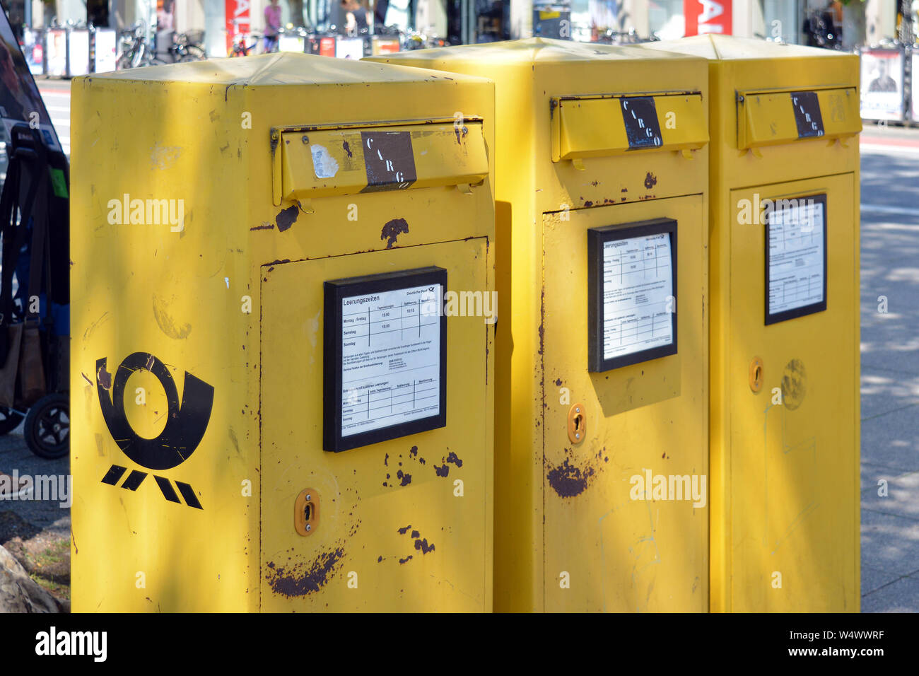 Heidelberg, Germany - June 2019: Three yellow official public mail boxes in a bad state on street Stock Photo