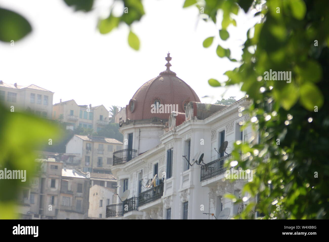 French colonial house with a dome, circled by tree leaves in Bejaia Algeria Stock Photo