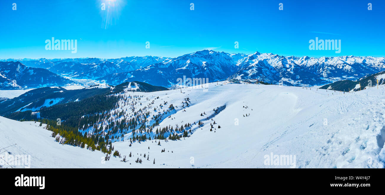 Observe the gentle snowy slopes of Schmitten mount with comfortable ski pistes and snowshoe routes, spruce forests and sharp rocks, Zell am See, Austr Stock Photo