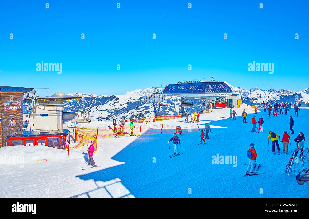 ZELL AM SEE, AUSTRIA - FEBRUARY 28, 2019: The skiers and boarders arrived to the top of Schmitten mountain on the ski lifts, covering its slopes, on F Stock Photo