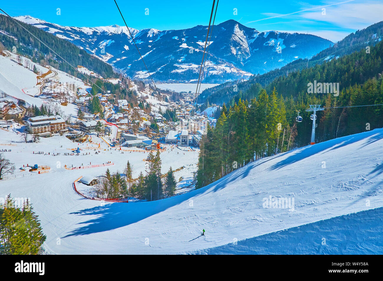 Aerial view on curved ski pistes, stretching along the snowy slope of Schmitten mount, lush coniferous forests and Zeller see valley with fozen lake a Stock Photo