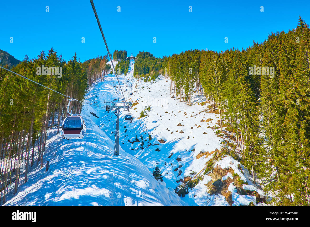 The snowy slope of Schmitten mount with lush pine forests and riding gondolas of Trassxpress cableway, Zell am See, Austria Stock Photo
