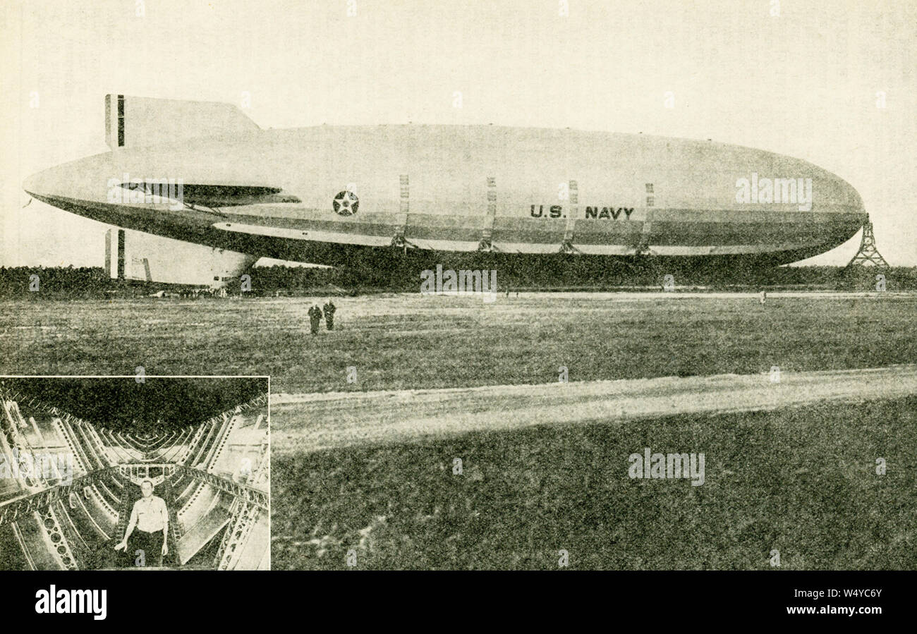 """The caption for this photo that dates to the first half of the 20th century reads: """"U.S.S. Akron - Warship of the Skies. This mighty dirigible, built for the United States Navy, was commissioned on Navy Day, October 27, 1931."""" If placed along a street, it would extend lengthwise over two city blocks, and upward to a ten-story building. A section of the control car is shown in the small picture. Stock Photo"""