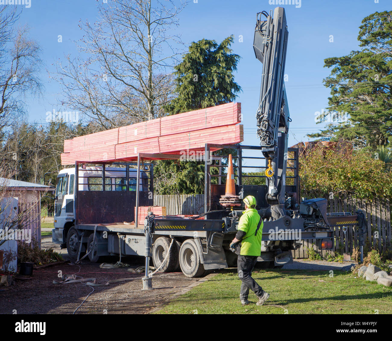 Sheffield. Canterbury, New Zealand, July 25 2019: Builders unload roof trusses that have been delivered by a Hiab truck to a building site Stock Photo
