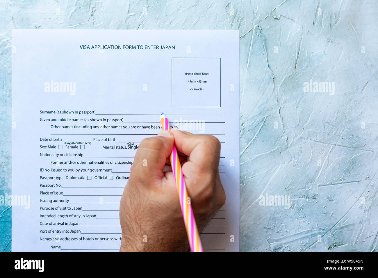 The person filling the Visa application form to enter Japan. Stock Photo